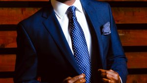 Black man looking good in a blue suit with white shirt and blue tie