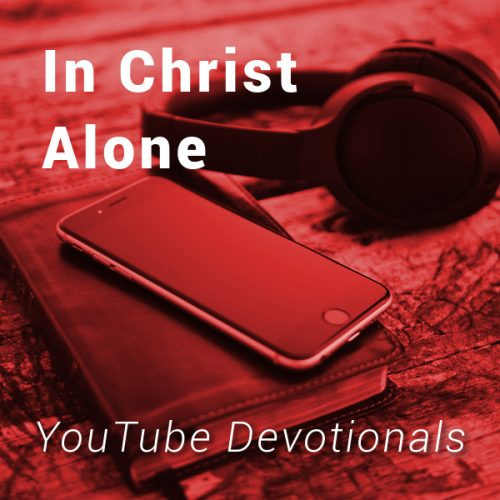 Bible, smart phone, headphones on table with text In Christ Alone YouTube Devotionals