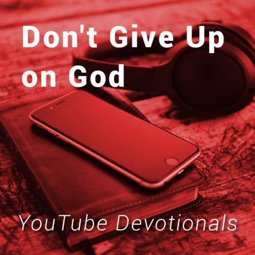 Bible, smart phone, headphones on table with text Don't Give Up on God YouTube Devotionals