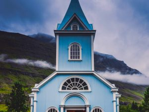 blue and white church in Iceland in front of mountains