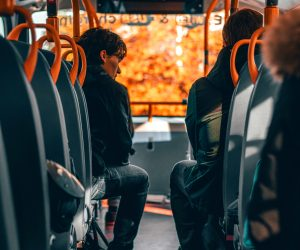 Two men sitting on a bus talking
