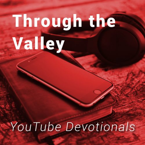 Bible, smart phone, headphones on table with text Through the Valley YouTube Devotionals