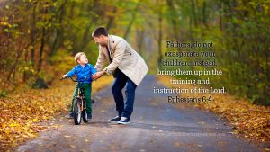 father teaching son to ride bike with Ephesians 6:4 desktop wallpaper