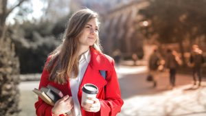 Woman in red coat walking with books and coffee