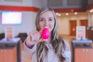 smiling woman in church holding pink plastic Easter egg