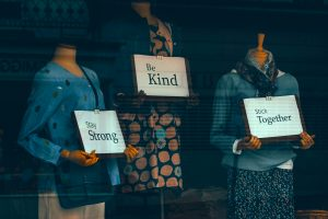 mannequins in store window holding signs stay strong be kind stick together