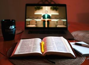 laptop streaming church service with Bible, notebook, and coffee cup