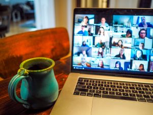 Laptop with Zoom video conference for small group on table next to coffee cup