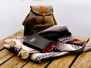 Bible, bag, and blanket on lake deck