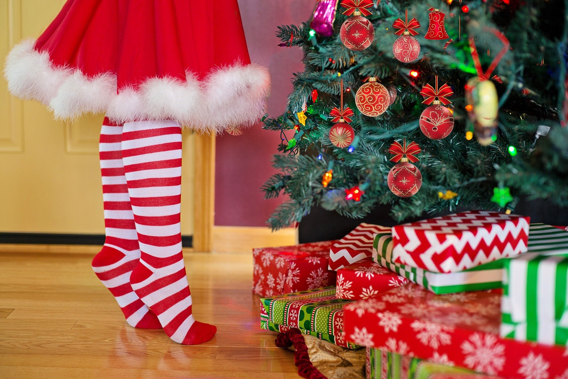 Girl wearing red dress and white and red striped socks decorating a Christmas tree with presents underneath it