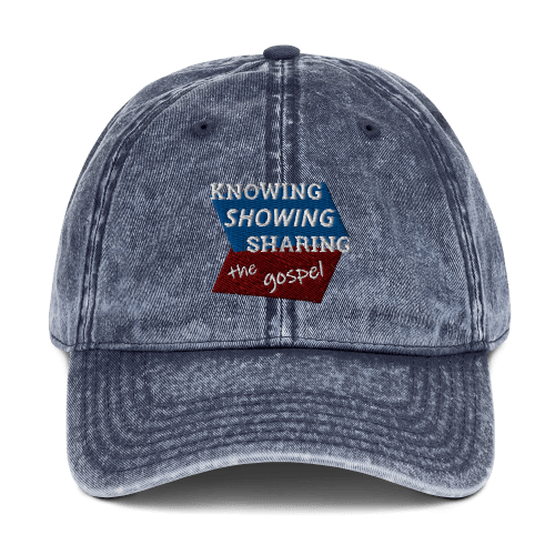 Blue denim-style baseball cap with Knowing Showing Sharing the gospel on blue and red background