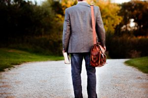 Man on a gravel road carrying a bag and a Bible for his Christian journey