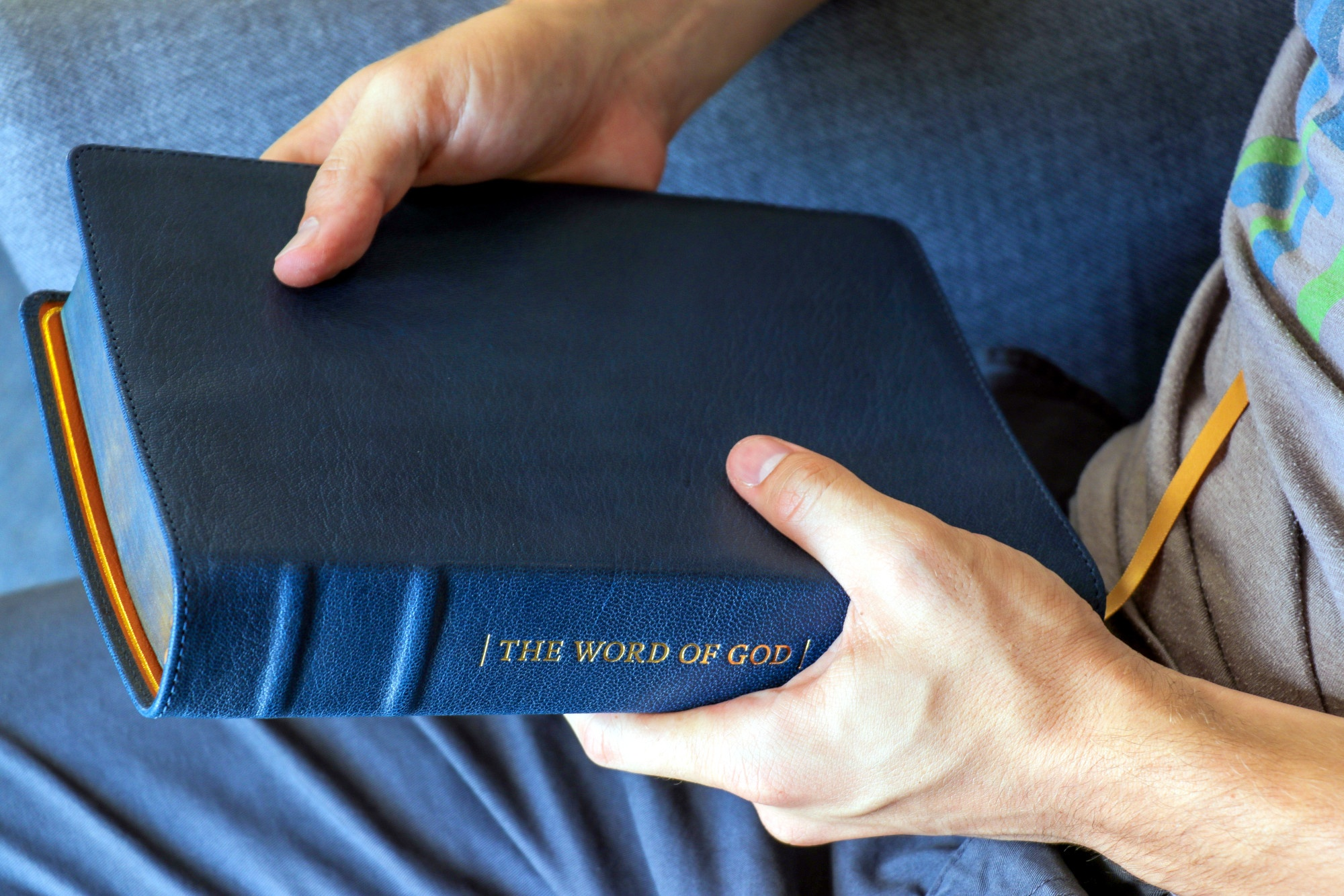 Man sitting holding a Bible with a blue leather cover